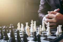Fermez-vous des collègues sûrs d'homme d'affaires de mains jouant des échecs Photographie stock