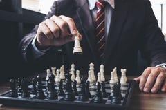Fermez-vous des collègues sûrs d'homme d'affaires de mains jouant des échecs Images stock