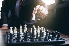Fermez-vous des collègues sûrs d'homme d'affaires de mains jouant des échecs Photos stock