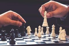 Fermez-vous des collègues sûrs d'homme d'affaires de mains jouant des échecs Image stock