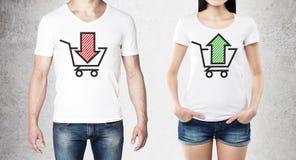 Fermez-vous des corps de l'homme et de la femme dans les T-shirts blancs avec deux croquis : un panier avec la flèche rouge et un Image stock