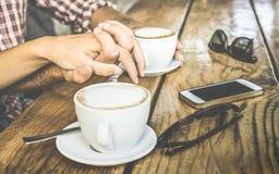 Fermez-vous des couples d'amour buvant du cappuccino frais au café Images libres de droits