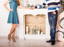 Fermez-vous des couples dans l'amour tenant des mains près d'une cheminée Photographie stock libre de droits
