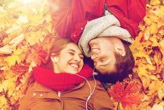 Fermez-vous des couples de sourire se situant en parc d'automne Images stock