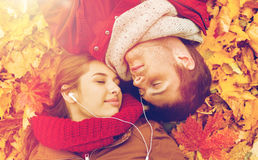 Fermez-vous des couples de sourire se situant en parc d'automne Photographie stock