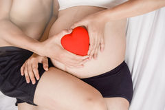 Fermez-vous des couples enceintes affectueux sur le lit avec le coeur Image libre de droits
