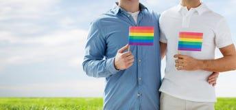 Fermez-vous des couples gais masculins tenant des drapeaux d'arc-en-ciel Photographie stock libre de droits