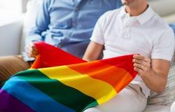Fermez-vous des couples gais masculins tenant le drapeau d'arc-en-ciel Photographie stock
