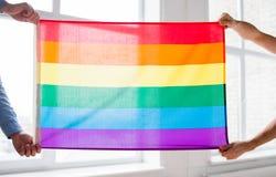 Fermez-vous des couples gais masculins tenant le drapeau d'arc-en-ciel Images libres de droits