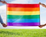Fermez-vous des couples gais masculins tenant le drapeau d'arc-en-ciel Photo stock