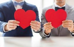 Fermez-vous des couples gais masculins tenant les coeurs rouges Images stock