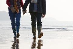 Fermez-vous des couples supérieurs marchant le long de la plage d'hiver Photographie stock