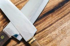 Fermez-vous des couteaux de cuisiniers et du hachoir en bois, WI de vue supérieure Image libre de droits