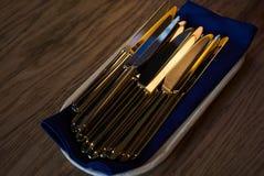 Fermez-vous des couteaux de vaisselle plate sur la table en bois images stock