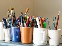 Fermez-vous des différents pinceaux utilisés, des crayons colorés affilés, des stylos, et des marqueurs Photographie stock libre de droits