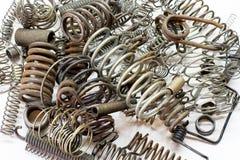 Fermez-vous des divers ressorts et bobines en métal sur le fond blanc Photo stock