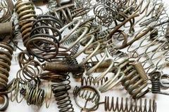 Fermez-vous des divers ressorts et bobines en métal sur le fond blanc Image stock