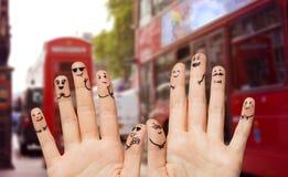 Fermez-vous des doigts avec épouser de visages de smiley Photographie stock