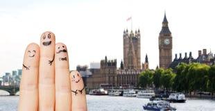 Fermez-vous des doigts avec les visages souriants au-dessus de Londres Photographie stock libre de droits