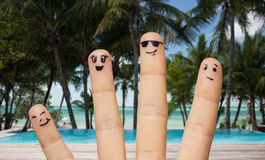 Fermez-vous des doigts avec les visages souriants sur la plage Photo libre de droits
