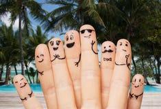 Fermez-vous des doigts avec les visages souriants sur la plage Photographie stock