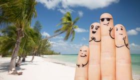 Fermez-vous des doigts avec les visages souriants sur la plage Photographie stock libre de droits