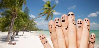 Fermez-vous des doigts avec les visages souriants sur la plage Image stock