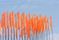 Fermez-vous des drapeaux oranges ébouriffés par le vent Photographie stock