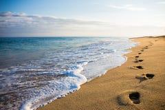 Fermez-vous des empreintes de pas dans le sable au coucher du soleil Photos stock