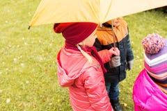 Fermez-vous des enfants avec le parapluie en parc d'automne Photo stock