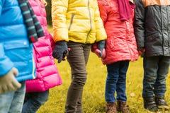 Fermez-vous des enfants tenant des mains en parc d'automne Photographie stock