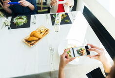 Fermez-vous des femmes décrivant la nourriture par des smartphones Photographie stock libre de droits
