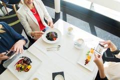 Fermez-vous des femmes décrivant la nourriture par des smartphones Image stock
