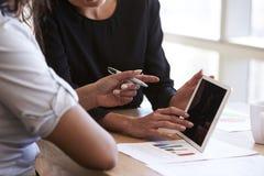 Fermez-vous des femmes d'affaires à l'aide de la Tablette de Digital lors de la réunion Photographie stock libre de droits