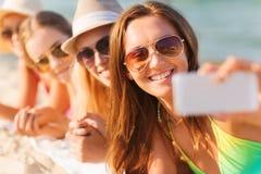 Fermez-vous des femmes de sourire avec le smartphone sur la plage Photographie stock libre de droits