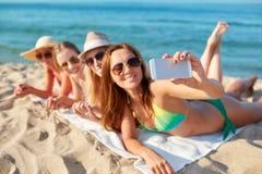 Fermez-vous des femmes de sourire avec le smartphone sur la plage Photos libres de droits