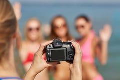 Fermez-vous des femmes de sourire photographiant sur la plage Image libre de droits