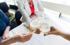 Fermez-vous des femmes faisant tinter le champagne au restaurant Images stock