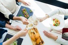 Fermez-vous des femmes faisant tinter le champagne au restaurant Photo libre de droits