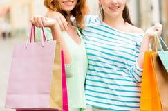 Fermez-vous des femmes heureuses avec des paniers dans la ville Image stock