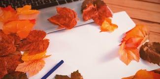 Fermez-vous des feuilles d'automne avec le papier par l'ordinateur portable images libres de droits