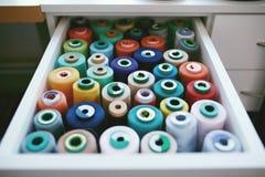 Fermez-vous des fils colorés de Sewig dans le tiroir Photo stock