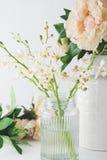 Fermez-vous des fleurs blanches d'orchidée dans un vase en verre avec des roses à b Photos stock