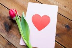 Fermez-vous des fleurs et de la carte de voeux avec le coeur Photo libre de droits
