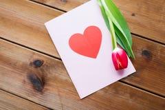 Fermez-vous des fleurs et de la carte de voeux avec le coeur Image stock