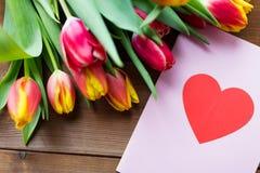 Fermez-vous des fleurs et de la carte de voeux avec le coeur Image libre de droits