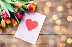 Fermez-vous des fleurs et de la carte de voeux avec le coeur Photographie stock libre de droits