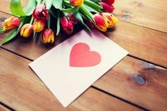 Fermez-vous des fleurs et de la carte de voeux avec le coeur Images stock