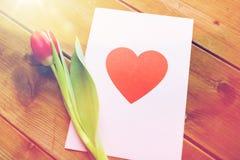 Fermez-vous des fleurs et de la carte de voeux avec le coeur Photographie stock
