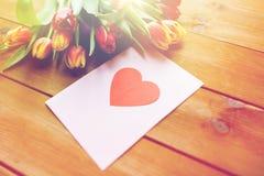Fermez-vous des fleurs et de la carte de voeux avec le coeur Photos libres de droits